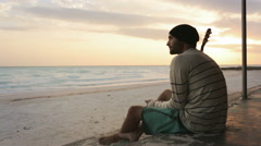 Young beautiful melancholy man on ocean beach seaside at sunrise Stock Footage