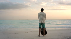 Young beautiful man stands up looking to ocean at beach seaside Stock Footage