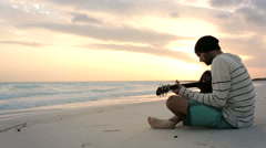 Young beautiful man tunes guitar at ocean beach seaside at sunrise - stock footage
