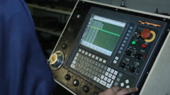 A factory worker at controls of machine with numerical control Stock Footage