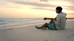 Young beautiful man plays guitar at ocean beach seaside at sunrise Stock Footage