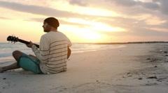Young beautiful man plays guitar at ocean beach seaside at sunrise Stock Footage