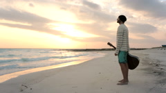 Young beautiful man stands up looking to ocean and sun at beach seaside Stock Footage