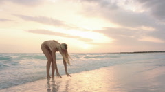 Young woman plays with water at sunrise or sunset Stock Footage