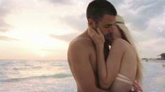 Young man woman couple in love hugs and kisses at ocean beach seaside Stock Footage