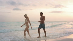 Side view of young man woman couple in love enjoys and walks Stock Footage