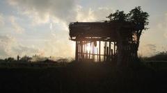 Silhouette of farmer's shack in stubble burning rice fields in Ubud Bali Stock Footage