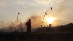 Silhouette of farmer burning stubble in rice field in Ubud Bali  during sunset Stock Footage