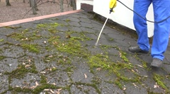 Worker man spray moss with chemicals on roof tiling Stock Footage