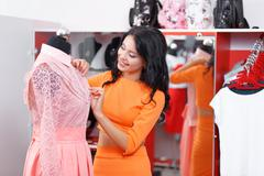 Beautiful young woman shopping in a clothing store Stock Photos
