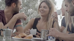 Group of four happy men and women friends smile, laugh and drink coffee Stock Footage