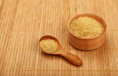 Scoop and bowl of brown cane sugar on mat Stock Photos