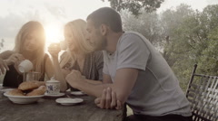 Group of three happy man and women friends smile, laugh and drink coffee - stock footage
