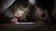 Two little girls sisters draw on a tablet PC hiding under a blanket Stock Footage