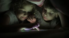 Two little girls sisters playing on a tablet PC hiding under a blanket Stock Footage