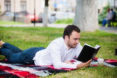 handsome young businessman reading book lying in the park - stock photo