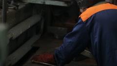 Welder in a protective helmet welded metal parts Stock Footage