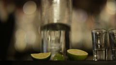 4K Close up on hands of barman pouring liquor into row of shot glasses - stock footage