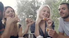 Group of four happy men and women friends smile, laugh, eat croissants - stock footage
