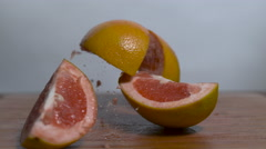 A sliced, grapefruit falls in slow motion onto a cutting board and separates Stock Footage