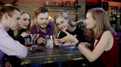 company of young people is watching something in the cellphone sitting in the - stock footage