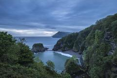 Beautiful moody sunrise landsape image of small secluded cove at Combe Martin - stock photo