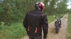 The countryside. Motorcyclist goes into full gear to his motorcycle Stock Footage