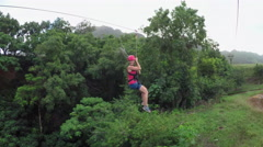 Young girl having fun while riding zipline cable above beautiful green jungle Stock Footage