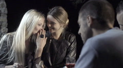 Young woman tell a secret to her friend and smile while enjoying aperitif Stock Footage