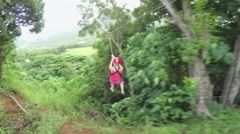 Young smiling girl sliding on cable high above lush jungle rainforest canopies Stock Footage