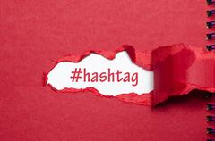 The word hashtag appearing behind torn paper - stock photo