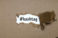 The word hashtag appearing behind torn paper Stock Photos