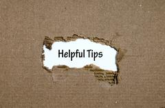 The word helpful tips appearing behind torn paper - stock photo
