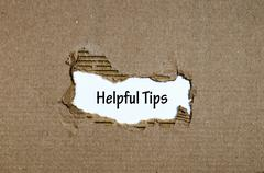 The word helpful tips appearing behind torn paper Stock Photos