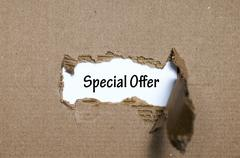 The word special offer appearing behind torn paper Stock Photos