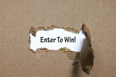 The word enter to win appearing behind torn paper - stock photo