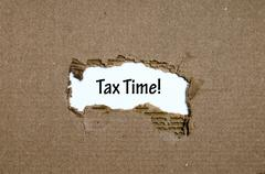 The word  tax time appearing behind torn paper Stock Photos