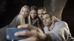 Group of four happy men and women friends shoot a selfie Stock Footage
