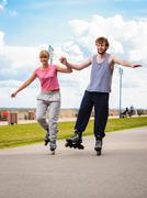 Active young people friends rollerskating outdoor. - stock photo