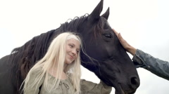 Blonde young woman smiles, strokes and hugs black horse outdoor Stock Footage