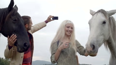 Young man and woman friends make a selfie with white and black horses Stock Footage
