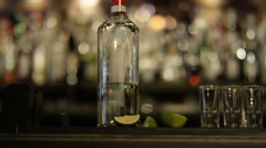 4K Smiling barman pouring liquor into row of shot glasses - stock footage