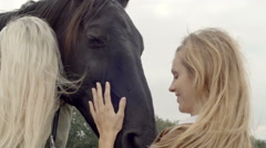 Two young women smiles, strokes and hugs black horse outdoor Stock Footage