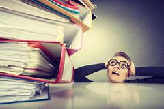 Accountant terrified of pils of binders. - stock photo