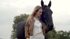 Young woman smiles, hugs black horse outdoor  gimbal steadicam Stock Footage