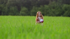 Little girl with ball running cross the green field at sunset.Slow motion Stock Footage