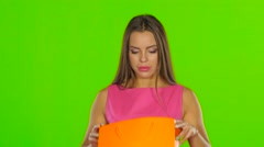 Woman looks at the package and consider buying. Green screen. Close up - stock footage