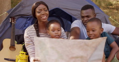 Family looking at map card in front of a tent Stock Footage