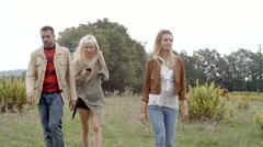 Three friends walk toward camera outdoor with horses  gimbal steadicam Stock Footage