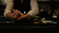 4K Barman using a match to set light to row of shot glasses with clear liquor - stock footage